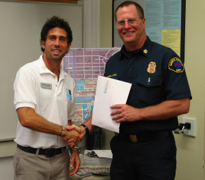 former City of Santa Monica Fire Chief Jim Hone accepts his I Am Santa Monica Completion Packet