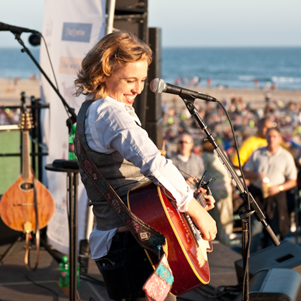 Woman singing and playing guitar onstage at Twilight on the Pier