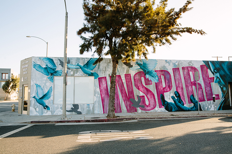 """""""Inspire"""" mural with birds adjacent to a person"""