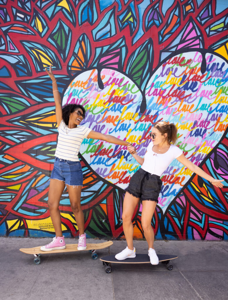 Two girls in front of a mural of a heart filled with Love