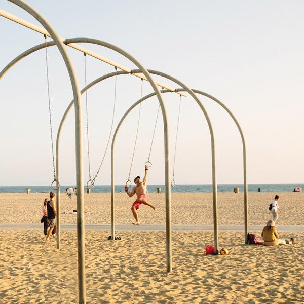 Man swinging on rings at Original Muscle Beach