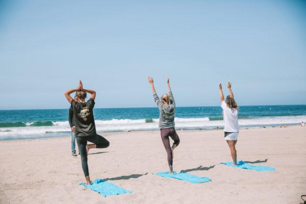 Three woman doing yoga on Santa Monica Beach