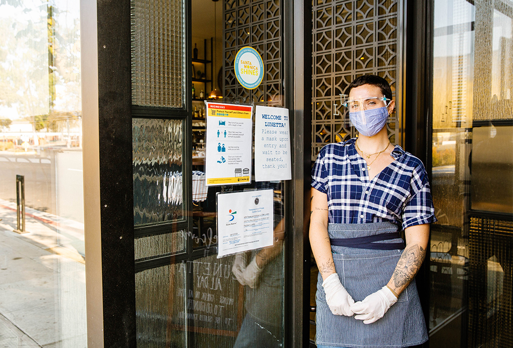 Lunetta employee standing in front of restaurant with Santa Monica Shines COVID-19 Assurance seal on the window
