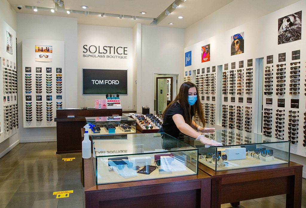 Staff member cleaning the counter at Solstice Sunglasses in Santa Monica