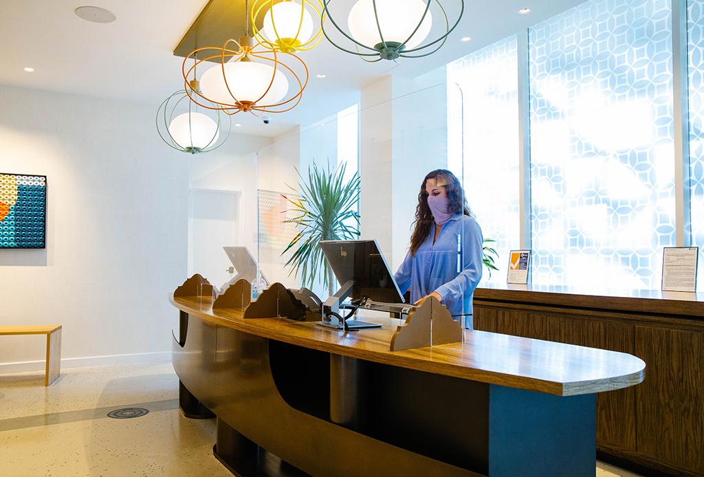 Viceroy Santa Monica front desk employee wearing mask standing at desk behind plexiglass separator