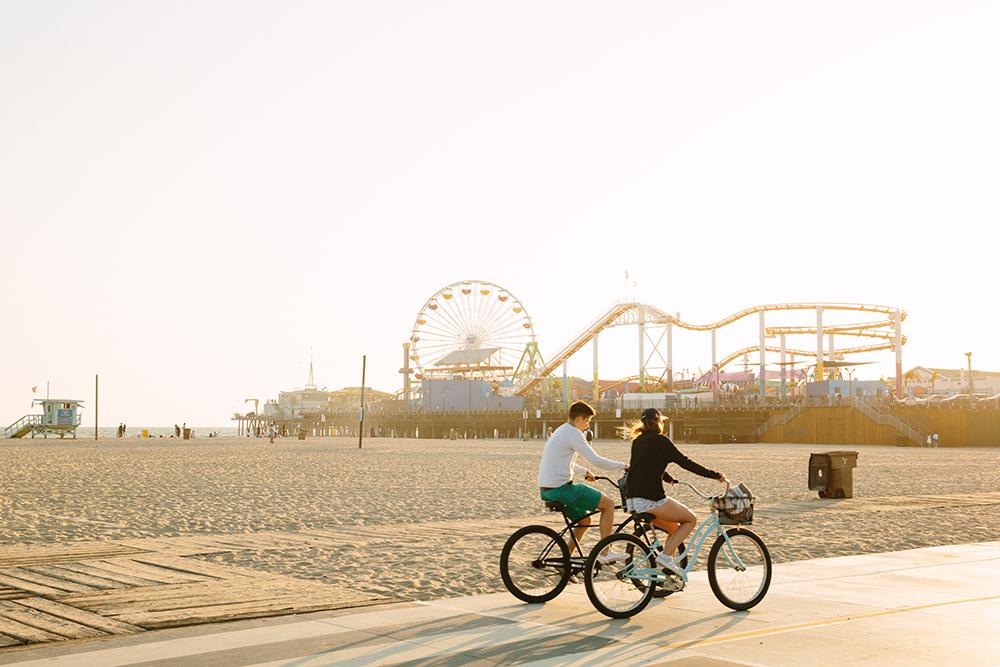Two people riding bikes along Santa Monica beach