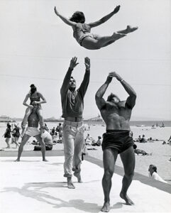 Acrobats throwing a girl in the air at Santa Monica Muscle Beach in 1953.